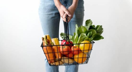 kobieta trzymająca koszyk z warzywami w dłoniach